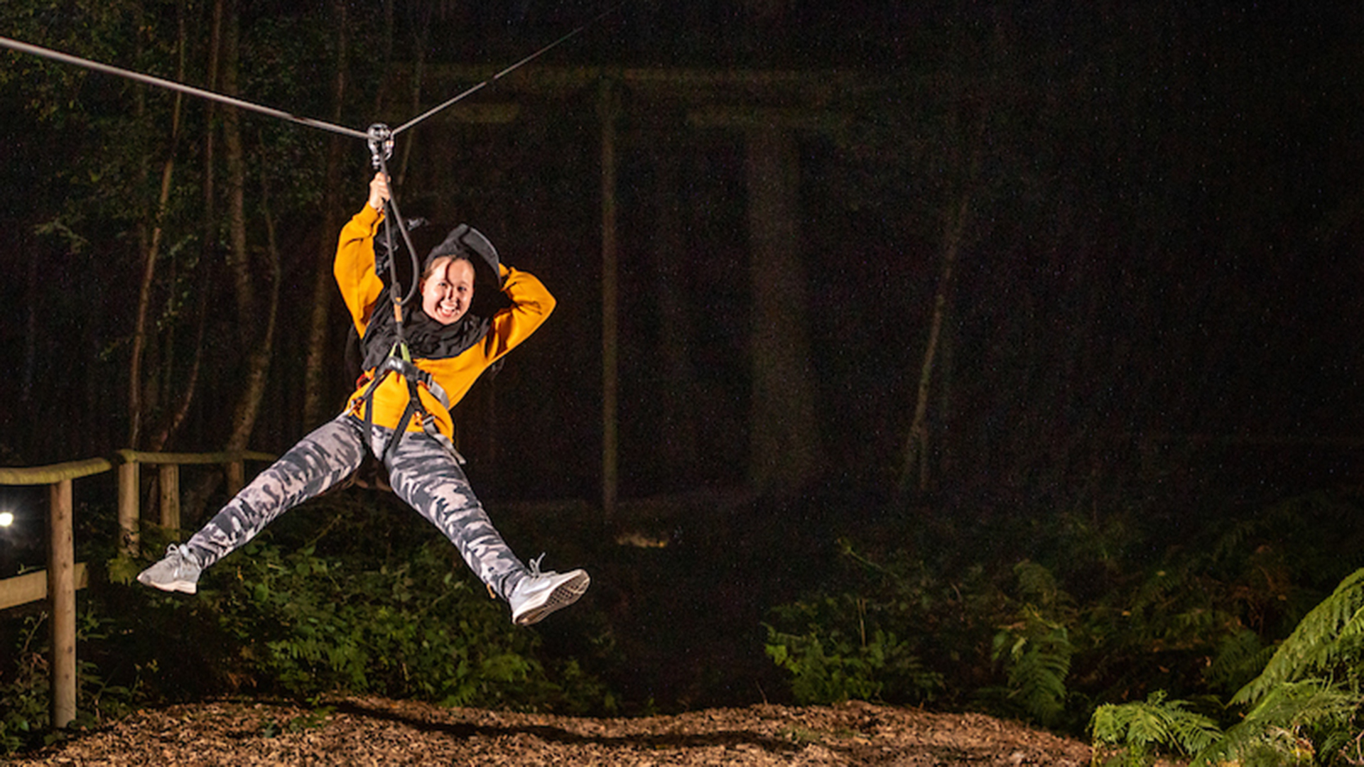 A person in yellow landing on a zip wire in the dark