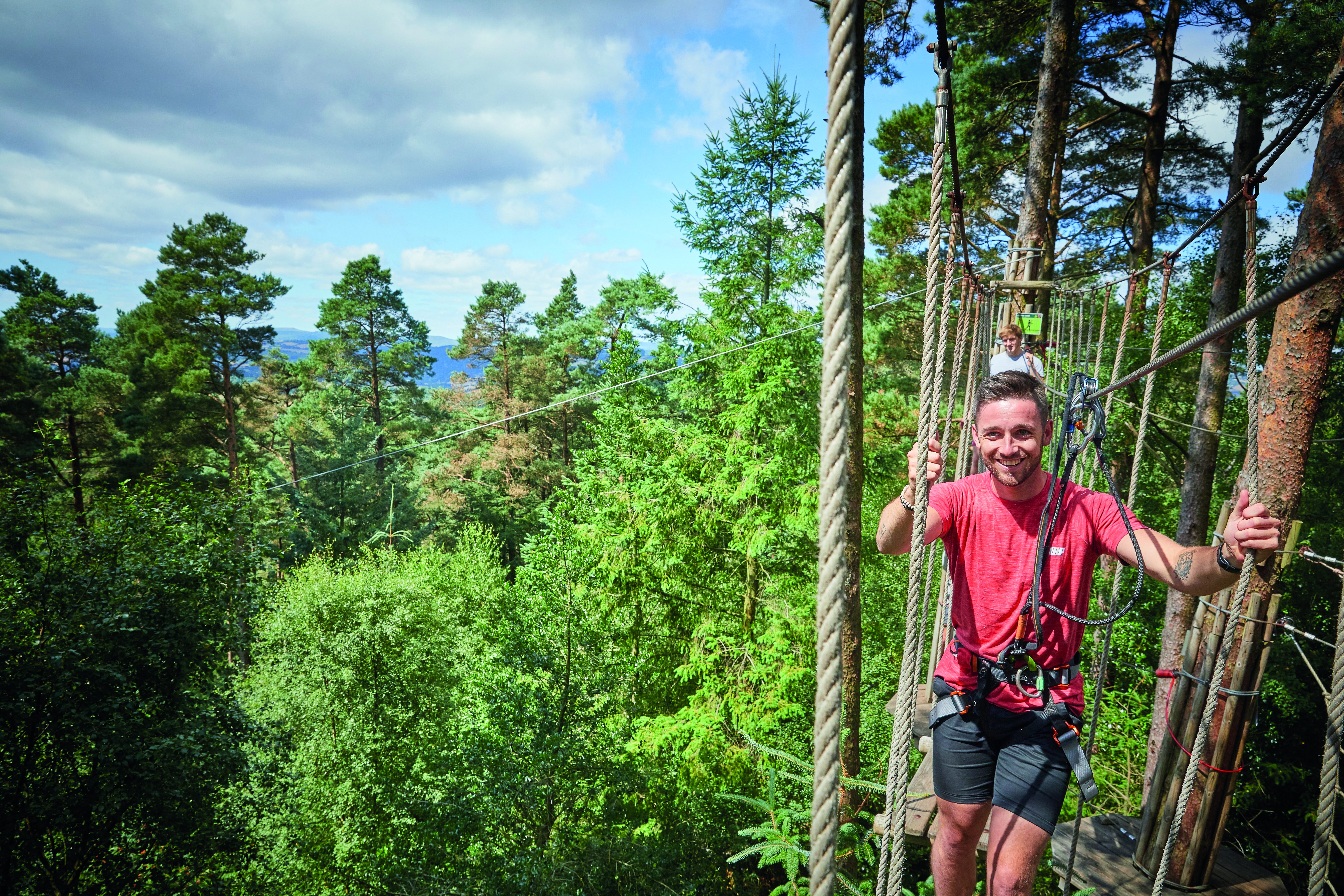 Man in red t-shirt on a Go Ape crossing