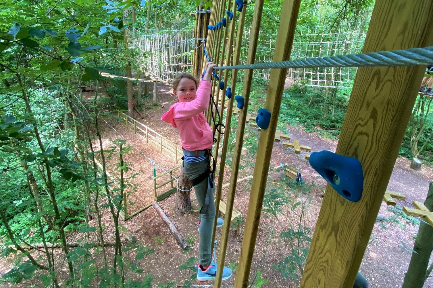 Girl in a pink top on a Go Ape crossing