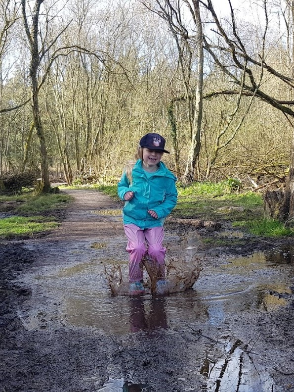 A child in waterprrof clothing splashing in a puddle