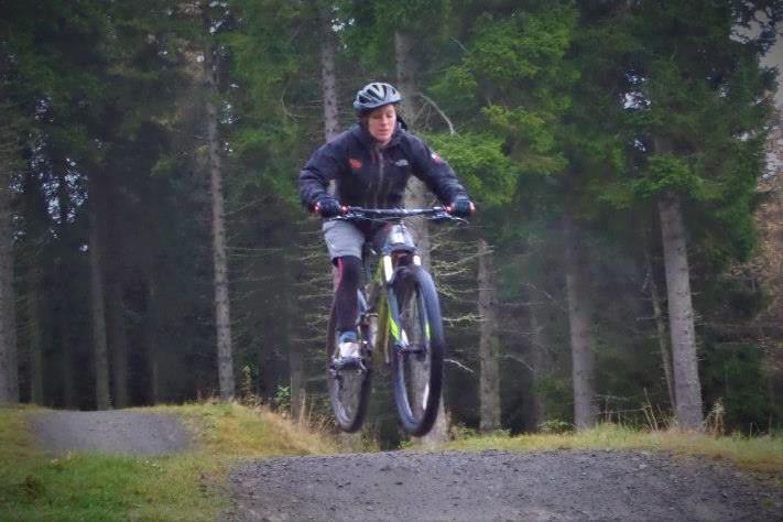 Woman on a mountain bike in Go Ape uniform