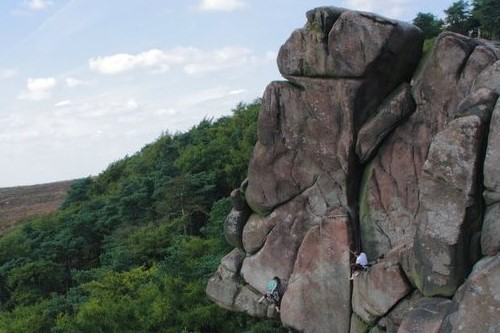 A rock climbing crag with two climbers ascending